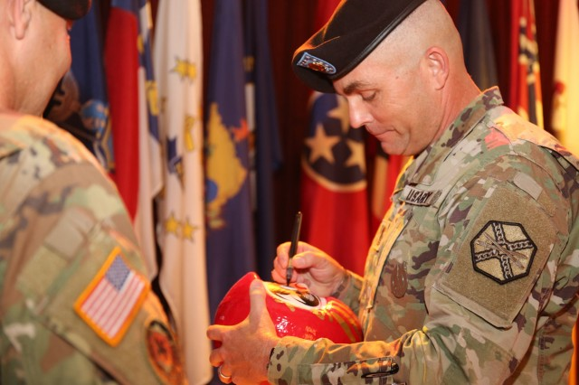 "Command Sgt. Maj. Will Holland colors in the eye of a Japanese ""Daruma"" doll to symbolize the achievement of his goals as part of his relinquishment of responsibility ceremony July 11, 2018, at the Camp Zama Community Club. Holland is headed to Washington, D.C., to serve as a liaison between the U.S. Army and the U.S. Department of Education. (U.S. Army photo by Noriko Kudo)"