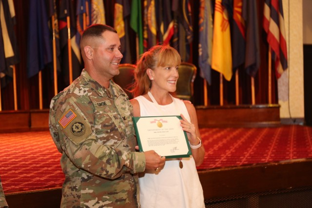 Col. Phillip Gage, USAG Japan commander, presents Wendy Holland with an Outstanding Civilian Service Award for her dedication and volunteerism in the community during an informal ceremony before her husband's relinquishment of responsibility ceremony July 11, 2018, at Camp Zama Community Club.  Her husband, outgoing Command Sgt. Maj. Will Holland, told ceremony attendees that Zama was the best duty station he had served at in his 32-year-career. (U.S. Army photo by Noriko Kudo)