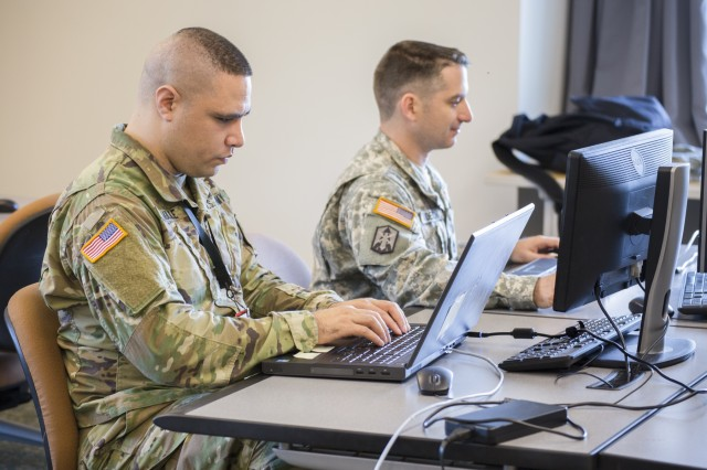 Spc. Sunia Laulile, Alpha Company, 156th Information Operations Battalion, 56th Theater Information Operations Group, and Sgt. 1st Class Samuel Anderson, Joint Force Headquarters, Washington National Guard, work to breach a network as an opposing force during the International Collegiate Cyber Defense Invitational, July 6, 2018, at Highline Community College in Des Moines, Wash.