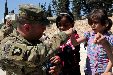 An information operations officer with U.S. Army Central teaches residents of the SOS Children's Village in Amman, Jordan, how to do a fist bump, April 23, 2018. Soldiers were part of a donation visit to the village that was arranged by Jordan Armed Forces Imams in coordination with U.S. Chaplains as part of ongoing coordination between the two partner nation militaries. Events like these help to build trust between service members and citizens of different nations.