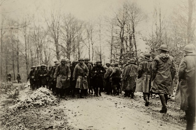 U.S. Army National Guard Soldiers from Company D, 1st Battalion, 165th Infantry, formerly the 69th Infantry of the New York National Guard, pass French Soldiers on the road from duty in the trenches on the Western Front near Benemenil, France, March 1, 1918.