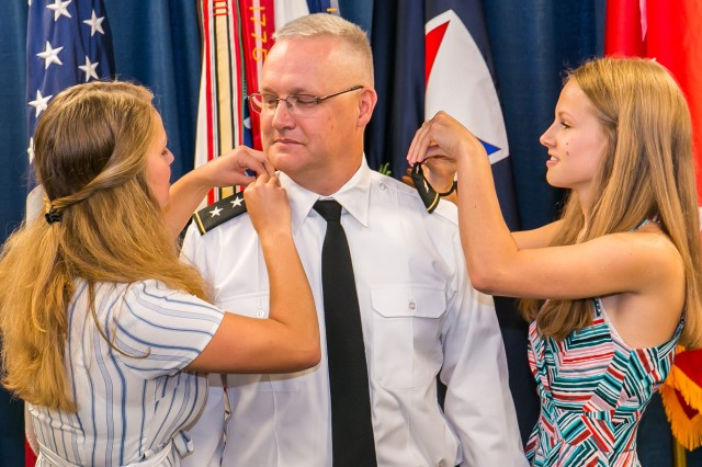 Maj. Gen. Paul Pardew watches as daughters Virginia and Samantha Pardew attach his new rank. Pardew is the U.S. Army Contracting Command commander.