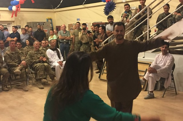 Mohammad Yahya Faqiri, right, a linguist for Train, Advise and Assist Command-South, comprised of the 40th Infantry Division, California National Guard, and the 2nd Infantry Brigade Combat Team, 4th Infantry Division, demonstrates a traditional Afghan dance with another linguist during Eid al-Fitr, a celebration, on Kandahar Airfield, Afghanistan, June 18. Eid al-Fitr, known as Eid for short, is a celebration marking the end of Ramadan, locally known as Ramazan, Islam's holy month of fasting.(U.S. Army photo by Maj. Richard Barker/TAAC-South Public Affairs)