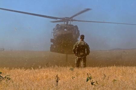 A Green Beret from 10th Special Forces Group (Airborne) stands by as a UH-60 lands near Chatfield Reservoir, outside of Littleton, Colo., June 28, 2018. Soldiers from 10th Special Forces Group honed their ability to perform static-line jumps and helocast into the reservoir, thereby sharpening the unit's ability to operate on land, sea, and air.