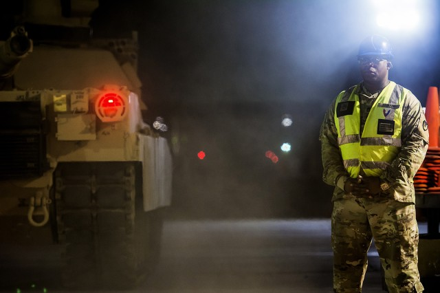 Sgt. 1st Class Robert Stinson, quality assurance specialist, Army Field Support Battalion-Kuwait, observes as two companies worth of M1A2 Abrams Main Battle Tanks move from an Army Prepositioned Stocks-5 warehouse to a remote lot, June 29, at Camp Arifjan, Kuwait. The vehicles are part of APS-5's ABCT equipment set. APS-5 is managed and maintained by the 401st Army Field Support Brigade. This equipment draw of APS-5's newly configured for combat ABCT marks the largest ever draw from APS-5. (U.S. Army photo by Justin Graff, 401st AFSB Public Affairs)