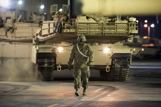 Soldiers assigned to the 155th Armored Brigade Combat Team move two companies worth of M1A2 Abrams Main Battle Tanks from an Army Prepositioned Stocks-5 warehouse to a remote lot, June 29, at Camp Arifjan, Kuwait. The vehicles are part of APS-5's ABCT equipment set. APS-5 is managed and maintained by the 401st Army Field Support Brigade. This equipment draw of APS-5's newly configured for combat ABCT marks the largest ever draw from APS-5. (U.S. Army photo by Justin Graff, 401st AFSB Public Affairs)