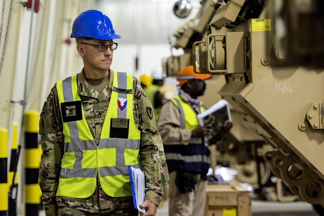 Sgt. 1st Class Richard Zulkowsky, quality assurance specialist, Army Field Support Battalion-Kuwait, walks through an Army Prepositioned Stocks-5 warehouse, July 1, at Camp Arifjan, Kuwait. The vehicles are part of APS-5's ABCT equipment set. APS-5 is managed and maintained by the 401st Army Field Support Brigade. This equipment draw of APS-5's newly configured for combat ABCT marks the largest ever draw from APS-5. (U.S. Army photo by Justin Graff, 401st AFSB Public Affairs)