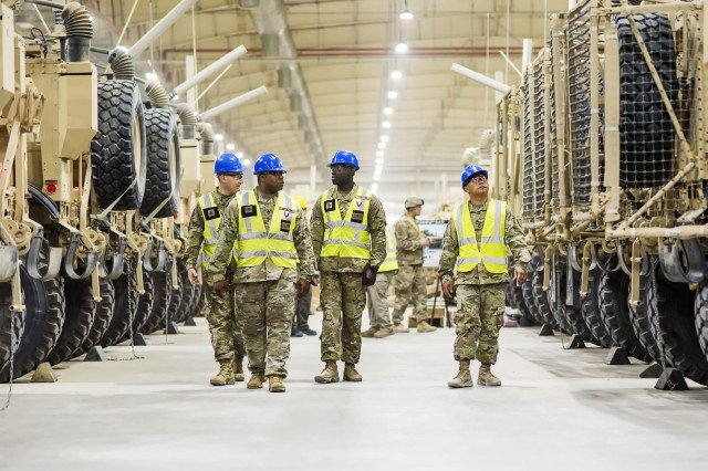 Army Field Support Battalion-Kuwait Quality Assurance Specialists walk through an Army Prepositioned Stocks-5 warehouse, July 1, at Camp Arifjan, Kuwait. The vehicles are part of APS-5's ABCT equipment set. APS-5 is managed and maintained by the 401st Army Field Support Brigade. This equipment draw of APS-5's newly configured for combat ABCT marks the largest ever draw from APS-5. (U.S. Army photo by Kevin Fleming, 401st AFSB Public Affairs)