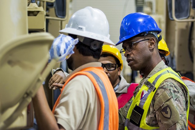 Sgt. 1st Class Dennis Spencer, quality assurance specialist, Army Field Support Battalion-Kuwait, talks with a contracted maintenance support team at an Army Prepositioned Stocks-5 warehouse, June 24, at Camp Arifjan, Kuwait. The vehicles are part of APS-5's ABCT equipment set. APS-5 is managed and maintained by the 401st Army Field Support Brigade. This equipment draw of APS-5's newly configured for combat ABCT marks the largest ever draw from APS-5. (U.S. Army photo by Justin Graff, 401st AFSB Public Affairs)