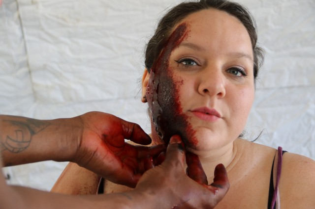 180712-D-WR005-376 JOINT BASE PEARL HARBOR-HICKAM, Hawaii (July, 12, 2018) Dawnn Villarreal, A Queens Medical Center accounts payable staff member and volunteer patient actor, receives moulage, or simulated facial lacerations, from a Tripler Army Medical Center medic during the U.S. Navy's Rim of the Pacific (RIMPAC) exercise, as part of the humanitarian assistance and disaster relief portion of the training event. Regional Health Command-Pacific Soldiers and civilians participated in the statewide medical response training to enhance operability, test communication and exercise crisis response capabilities amongst interagency partners. Twenty-five nations, 46 ships, five submarines, about 200 aircraft and 25,000 personnel are participating in RIMPAC from June 27 to Aug. 2 in and around the Hawaiian Islands and Southern California. The world's largest international maritime exercise, RIMPAC provides a unique training opportunity while fostering and sustaining cooperative relationships among participants critical to ensuring the safety of sea lanes and security of the world's oceans. RIMPAC 2018 is the 26th exercise in the series that began in 1971. (U.S. Army photo by Ana Allen/Released)