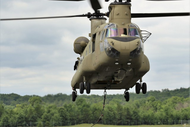 An aircrew of a Chinook helicopter picks up a mock ammunition pallet after it was connected to the helicopter June 27, 2018, as part of sling load training for the 89B Ammunition Supply Course at Sparta-Fort McCoy Airport at Fort McCoy, Wis. The Ammunition Supply Course, taught by the 13th Battalion, 100th Regiment at Fort McCoy, is a four-week course that provides training for Soldiers who are reclassifying to the 89B military occupational specialty. The sling-load training is one of the last major training events during the course. A sling load is used to transport munitions to remote locations or to expedite shipments in hostile locations. The 13th, 100th is an ordnance battalion that provides training and training support to Soldiers in the ordnance maintenance MOS series. The unit, aligned under the 3rd Brigade, 94th Division of the 80th Training Command, has been at Fort McCoy since about 1995. (U.S. Army Photo by Scott T. Sturkol, Public Affairs Office, Fort McCoy, Wis.)