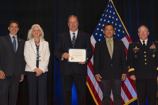 Employees of the Armament Research, Development and Engineering Center accept the Department of Defense Value Engineering Award on behalf of the Apache Production and Fielding Value Engineering Team during a June 28, 2018 awards ceremony at the Pentagon. Presenting the award are Kristen Baldwin, acting deputy assistant secretary of Defense Systems Engineering, and Maj. Gen. Brian Cummings, Program Executive Officer for Ground Combat Systems. (U.S. Army photo by Zane Ecklund)