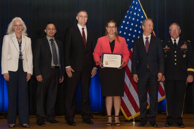 Employees of the Project Manager, Combat Ammunition Systems, Picatinny Arsenal. N.J./Rock Island Arsenal, Ill., accept the Department of Defense Value Engineering Award on behalf of the Apache Production and Fielding Value Engineering Team during a June 28, 2018 awards ceremony at the Pentagon. Presenting the award are Kristen Baldwin, acting deputy assistant secretary of Defense Systems Engineering, and Maj. Gen. Brian Cummings, Program Executive Officer for Ground Combat Systems.