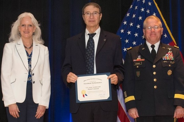 Tom Reynolds, who manages the Value Engineering Program at Redstone Arsenal, accepts a Department of Defense Value Engineering Award on behalf of the Aviation and Missile Command in the organization category during a June 28 awards ceremony at the Pentagon. This is the third year in a row that AMCOM has won the organization award. This year's award recognizes the completion of 98 Value Engineering projects representing $216 million in savings over a three-year period. Presenting the award to Reynolds are Kristen Baldwin, acting deputy assistant secretary of Defense Systems Engineering, and Maj. Gen. Brian Cummings, e Program Executive Officer for Ground Combat Systems.