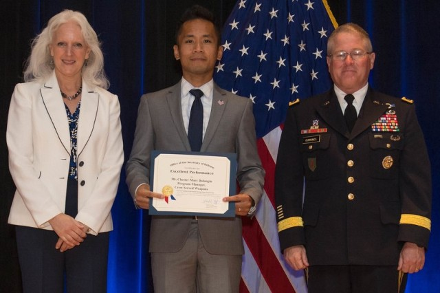 Chester Marc Dalangin, Product Director, Precision Weapon Optics, Fire Control and Accessories, Product Manager Crew Served Weapons, Program Executive Office for Soldier, Picatinny Arsenal, accepts the Department of Defense Value Engineering Award on behalf of the Apache Production and Fielding Value Engineering Team during a June 28, 2018, awards ceremony at the Pentagon. Presenting the award are Kristen Baldwin, acting deputy assistant secretary of Defense Systems Engineering, and Maj. Gen. Brian Cummings, Program Executive Officer for Ground Combat Systems.