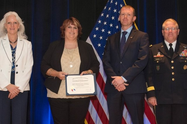 Kora Davis and Nathan Kennedy, both of the Program Executive Office for Aviation, accept the Department of Defense Value Engineering Award on behalf of the Apache Production and Fielding Value Engineering Team during a June 28 awards ceremony at the Pentagon. Presenting the award are Kristen Baldwin, acting deputy assistant secretary of Defense Systems Engineering, and Maj. Gen. Brian Cummings, Program Executive Officer for Ground Combat Systems.