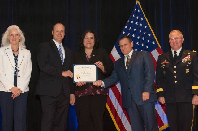 Employees of Project Manager, Armored Fighting Vehicles accept the Department of Defense Value Engineering Award on behalf of the Apache Production and Fielding Value Engineering Team during a June 28 awards ceremony at the Pentagon. Presenting the award are Kristen Baldwin, acting deputy assistant secretary of Defense Systems Engineering, and Maj. Gen. Brian Cummings, Program Executive Officer for Ground Combat Systems.