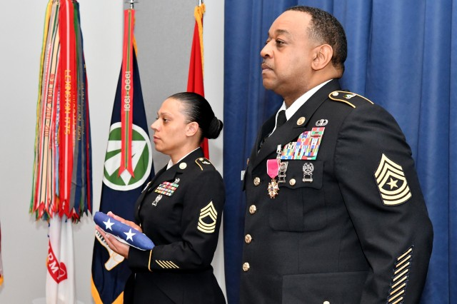 Sgt. Maj. Torrance Braswell, the Military Surface Deployment and Distribution Command's Operations Sergeant Major, is presented a ceremonial American flag by Master Sgt. Danielle Archer during his retirement ceremony at Scott Air Force Base, Illinois, July 13.