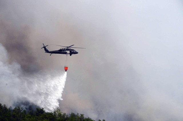 A New York Army National Guard UH-60 assigned to 3rd Battalion, 142nd Aviation, delivers 660 gallons of water onto a forest fire in Flat Rock State Forest in Altona, N.Y. on July, 13, 2018.