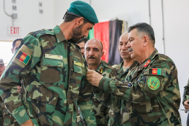 Afghan National Army Brig. Gen. Abdul Rahman Parwani, right, deputy commander of the 205th Corps, right, places a new patch on an Afghan soldier, July 5, 2018, during the Eagle Strike Company graduation ceremony in Camp Hero, Afghanistan.
