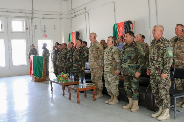 Afghan and U.S. Army senior leaders stand for the Afghanistan National Anthem, July 5, 2018, during the Eagle Strike Company graduation ceremony at Camp Hero, Afghanistan.