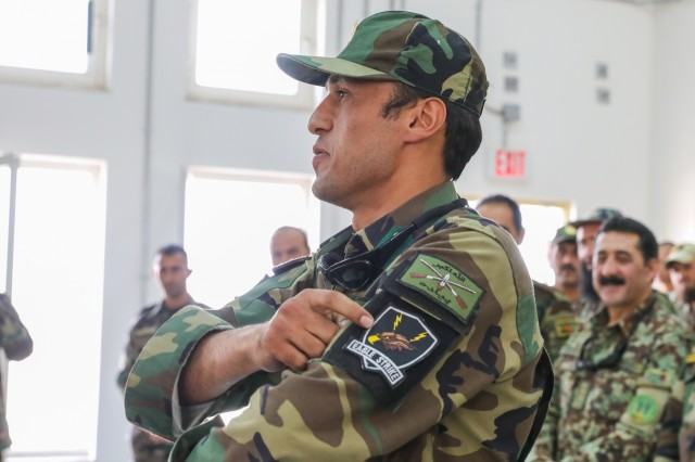 An Afghan army soldier points to his new patch, July 5, 2018, during the Eagle Strike Company graduation ceremony in Camp Hero, Afghanistan.