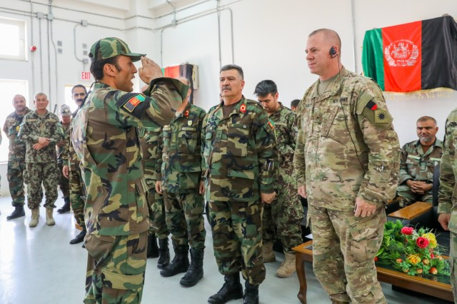 An Afghan soldier, left, salutes U.S. Army Brig. Gen. Jeffrey Smiley, right, commanding general for Train, Advise and Assist Command-South, July 5, 2018, during the Eagle Strike Company graduation ceremony in Camp Hero, Afghanistan.