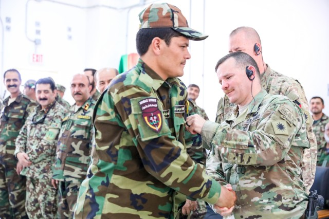 U.S. Army Col. David Abrahams, right, senior advisor for the Afghan National Army 205th Corps, places an Eagle Strike Company patch on an Afghan Army soldier, July 5, 2018, during the company's graduation ceremony at Camp Hero, Afghanistan.