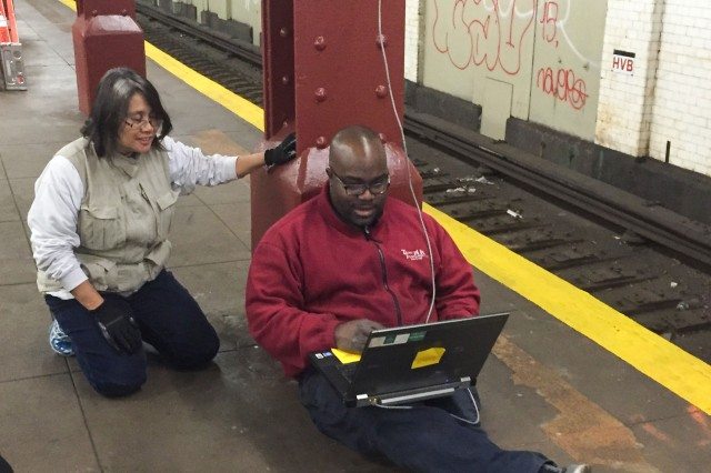 """Researchers install cables for transmission of motion-capture and video recording throughout a section of a subway platform and on several train cars at a transit station in a major U.S. city. TBRL conducts """"in vivo"""" testing in public locations such as theaters, religious buildings, schools, subways and sports stadiums."""
