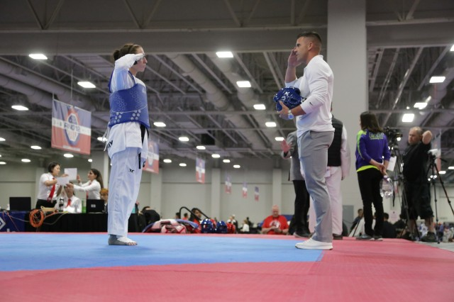 Spc. Devon Lewis saultes her coach Staff Sgt. David Bartlett before her final fight of the competition. Tradititionally in taekwondo, athletes bow to their coaches as a sign of respect but the WCAP and All Army athletes salute.