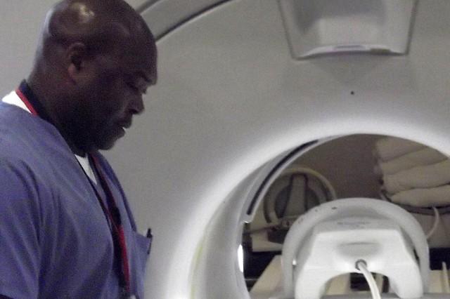 Derrick Taylor, an MRI tech at Ireland Army Health Clinic, readies a patient for an MRI