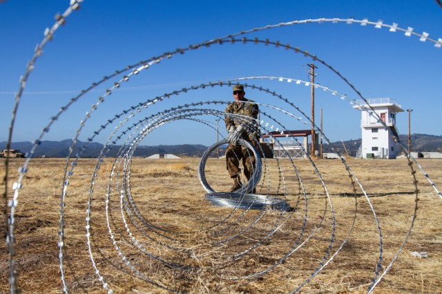 Arizona Army National Guard Staff Sgt. Ricardo Ramos creates a defensive perimeter with concertina wire around the tactical operations center June 28th 2018 at Fort Hunter Liggett, California. Ramos is a military policeman with the 198th Regional Support Group Headquarters and Headquarters Company which was at Fort Hunter Liggett for 21 days conducting their annual training.