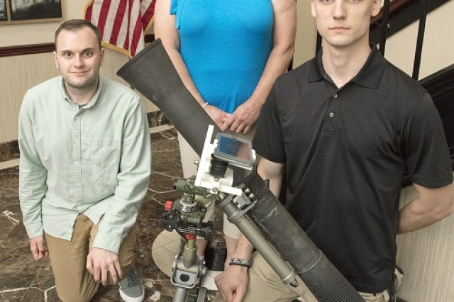 """PICATINNY ARSENAL, N.J. - From left, Matthew Brauer, Christine Plutta, and Ryan Petillo show a training device they fabricated after attending a recent Phase 4 """"Greening"""" course at the Maneuver Center of Excellence at Fort Benning, Georgia. The 3-D printed holder allows instructors to project what is visible through a mortar scope with the use of a cell phone. Not pictured is David Sabanosh."""