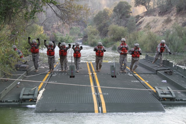 A launch and retrieve team from the 132nd Multirole Bridge Company, 579th Engineer Battalion, 49th Military Police Brigade, California Army National Guard, use a steel guide line to move a ramp and bay over Cache Creek River Aug. 7, 2015, at Cache Creek Regional Park in Yolo County, California.