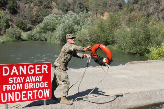 U.S. Army Spc. Christian Berg of the 132nd Multirole Bridge Company, 579th Engineer Battalion, 49th Military Police Brigade, California Army National Guard, tosses a floatation device to a teammate July 13, 2018 as members of the 132nd secure a temporary floating bridge at Cache Creek Regional Park, California.