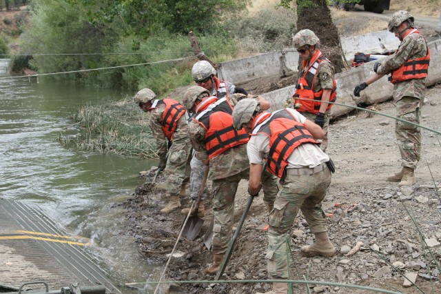 U.S. Army engineers from the 132nd Multirole Bridge Company (MRBC), 579th Engineer Battalion, 49th Military Police Brigade, California Army National Guard, unearth ground to reposition a ramp July 14, 2018 while dismantling a floating bridge at Cache Creek Regional Park, Yolo County, California.