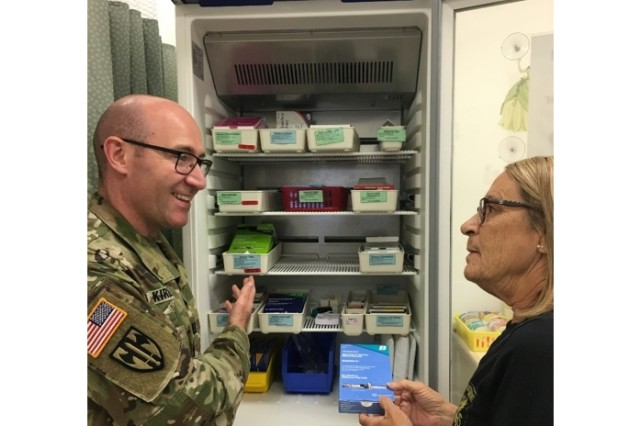Capt. William Kirby (left), chief of pharmacy at the Grafenwoehr Army Health Clinic, and an immunization nurse, Ms. Sheila Stiegman, discuss vaccine safety and the administration labels.