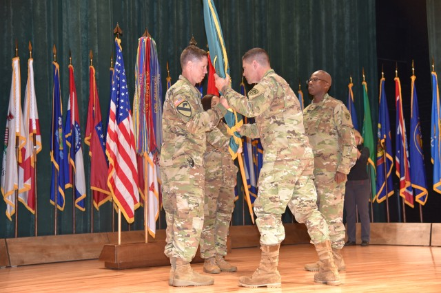 Maj. Gen. Joel K. Tyler, the U.S. Army Test and Evaluation Command commander, passes the U.S. Army Aberdeen Test Center, or ATC, flag to Commander Col. John F. Hall during ATC's change of command ceremony at the post theater at Aberdeen Proving Ground June 29.