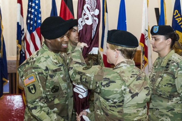 Col. Rebecca Porter, Public Health Command Europe Commander, passes the unit colors to Sgt. Maj. Kevin Buie, incoming PHCE Sgt. Maj, during a Change of Responsibility ceremony Friday, July 13. During the ceremony, Buie assumed responsibility from Master Sgt. Gina R. Egan.