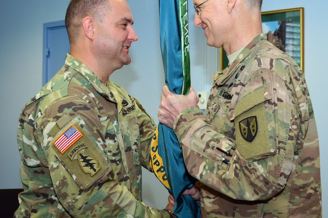 Incoming Col. Garrett Kolo receives the unit colors from Col. Stephen Smith, deputy commander of the U.S. Army Reserve Sustainment Command, during the change of command ceremony, July 13. (Photo by Linda Lambiotte, ASC Public Affairs)