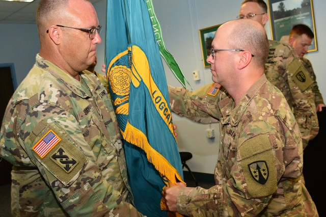 Lt. Col. Leonard Sloat, outgoing commander, passes the unit colors to incoming commander, Col. Garret Kolo, during the change of command ceremony, July 13. (Photo by Linda Lambiotte, ASC Public Affairs)