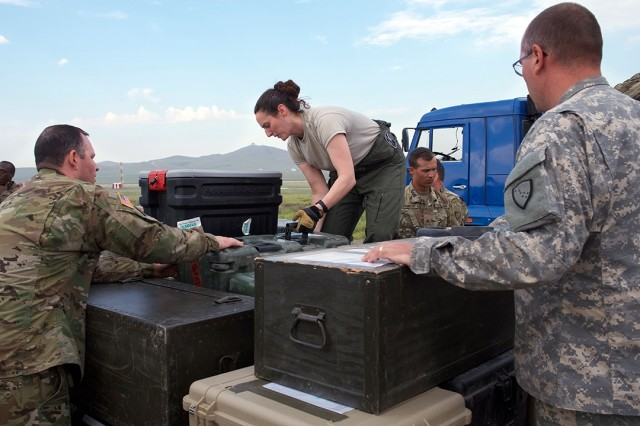 Alaska Air National Guard Tech Sgt. Jennifer Fitzpatrick (center), a loadmaster with the 249th Airlift Squadron, supervises Soldiers loading a cargo pallet June 30, 2018, at Chinggis Khaan International Airport, Mongolia, after the Soldiers participated in Khaan Quest 2018. Khaan Quest is a combined (multinational) joint (multi-service) training exercise designed to strengthen the capabilities of U.S., Mongolian and other partner nations in international peace support operations.