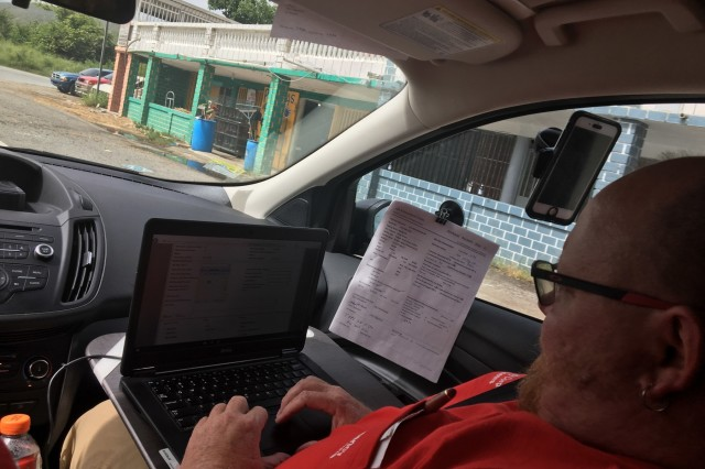A member of the Pittsburgh District temporary power team in Puerto Rico inputs data into the Englink system while in the field.