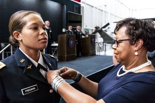 Retired Col. Christine Knighton pins aviator wings on 2nd Lt. Kayla Freeman at Freeman's graduation from the Army Aviation school, June 21, 2018, at Fort Rucker, Ala.