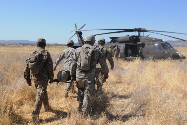 Soldiers from various units training in support of the Global Medic exercise at Fort Hunter Liggett, Calif., practice how to properly load a stretcher onto a HH-60M Blackhawk helicopter during a MEDEVAC 101 class, July 13, 2018.