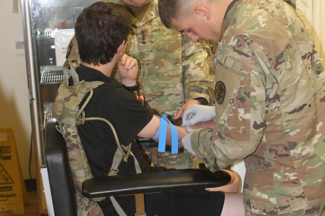 Chief of Staff of the Army Gen. Mark Milley puts questions to Pvt. Rickey Salinas while Pfc. Ethan Palmer, a medic assigned to the 95th Adjutant General (Reception) Battalion, draws blood during the general's July 11, 2018, to Fort Sill, Okla.
