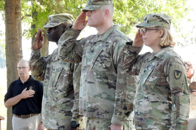 Col. Joseph Blanding, commander, McAlester Army Ammunition Plant, Lt. Col. Eric Dennis, commander, Lake City Army Ammunition Plant, and Lt. Col. Dana Crow, incoming LCAAP commander, salute during the playing of the National Anthem at the change of command ceremony in Independence, Mo., on July 12.