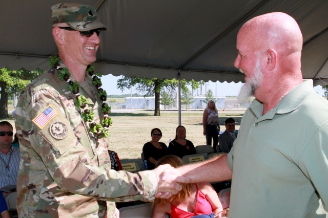 Lt. Col. Nathaniel Crow, spouse of incoming commander, Lt. Col. Dana Crow, is presented a lei and a handshake from Scott Hayes, a civilian employee at Lake City Army Ammunition Plant, at the beginning of the LCAAP change of command ceremony on July 12.