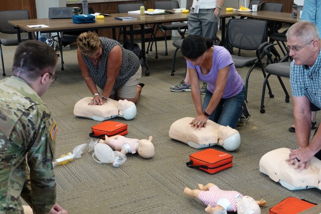 Radiologic Technologist Spc. James Wagner, Medical Department Activity, conducts basic life support training with special education teachers Becky Wenzel, Zinthia Brown and Paul Pursel July 17 at the United School District 207 building.