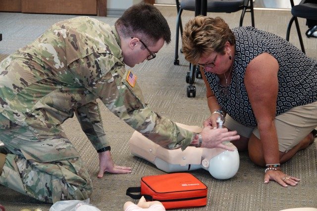 Radiologic Technologist Spc. James Wagner, Medical Department Activity, demonstrates proper hand technique putting on the face mask during a Basic Life Support training to Becky Wenzel, Special Education Teacher July 17 at the United School District 207 building.